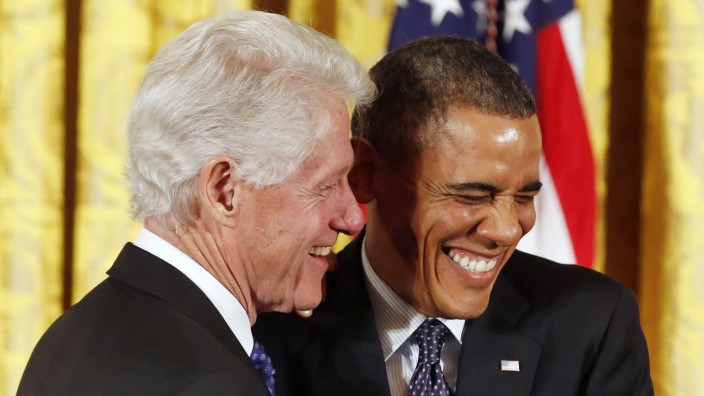 U.S. President Obama shares a laugh with former president Clinton before presenting him with the Presidential Medal of Freedom in Washington