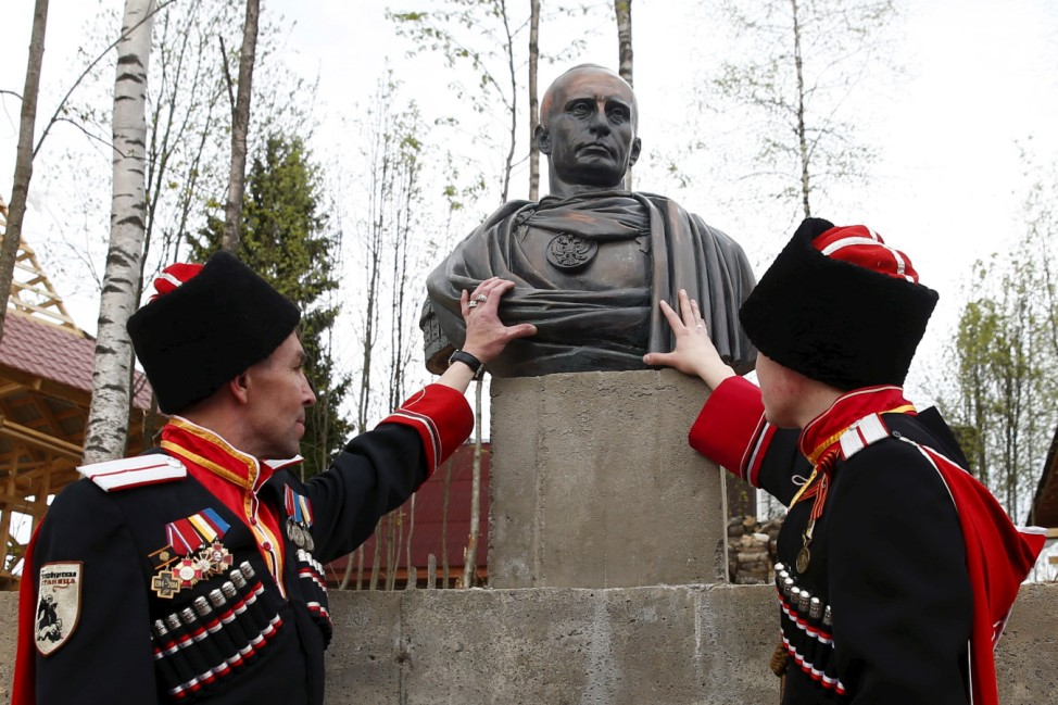 Cossacks stand next to bust of Russian President Putin during its unveiling ceremony in Leningrad region