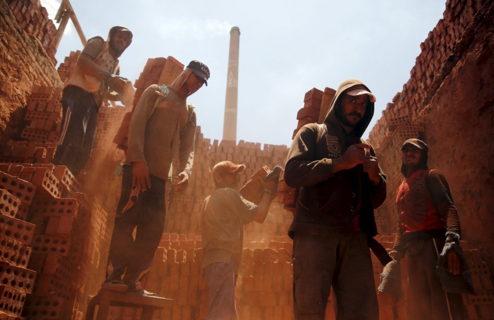 Labourers work at a traditional bricks factory in Arab Mesad district of Helwan, northeast of Cairo