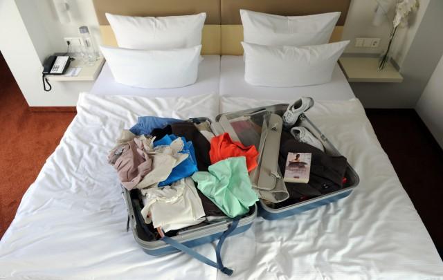 Ein gepackter Koffer auf einem Hotelbett