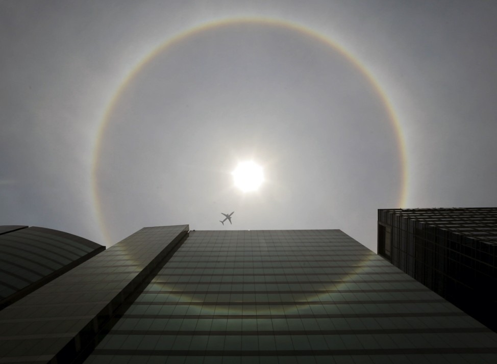A plane flies past a solar halo in Mexico City