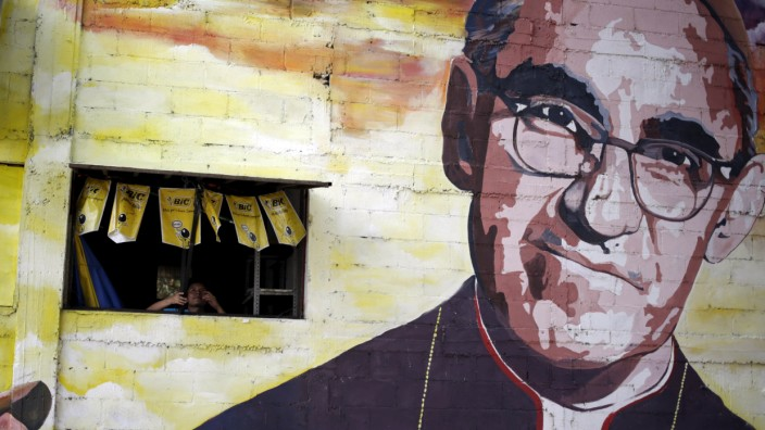 A man closes a window in the wall next to a mural of the late Salvadoran Archbishop Oscar Arnulfo Romero in Panchimalco