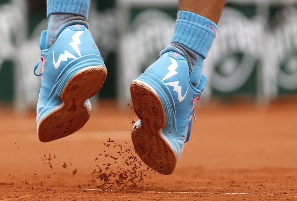The shoes of Rafael Nadal of Spain are seen as he jumps to serve to Quentin Halys of France during their men's singles match at the French Open tennis tournament at the Roland Garros stadium in Pari