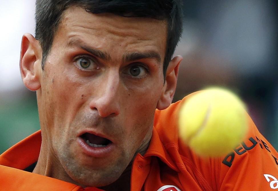Novak Djokovic of Serbia plays a shot to Jarkko Nieminen of Finland during their men's singles match at the French Open tennis tournament at the Roland Garros stadium in Paris