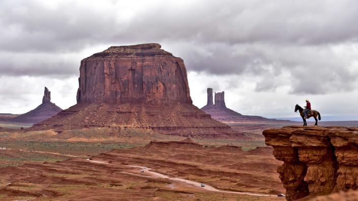 Ab-in-den-Urlaub.de und Fluege.de: Am John Ford's Point im Monument Valley posieren Navajo-Reiter für Touristen, das sieht gut aus auf den Urlaubsfotos. Aber wie dort hinkommen? Viele Menschen buchen ihre Reisen im Internet.
