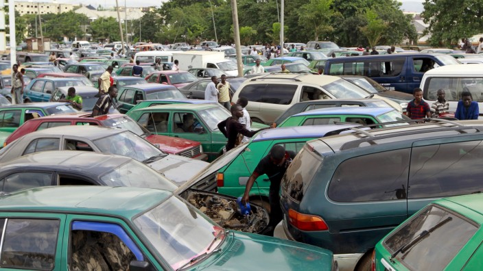 Man works on the engine of his car, as motorists gather at a petrol station of state-owned energy company Nigerian National Petroleum Corporation in Abuja, Nigeria