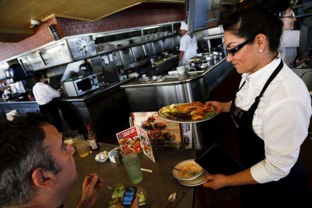 A waitress serves a steak and fried shrimp combo plate to a customer at Norms Diner on La Cienega Boulevard in Los Angeles, California