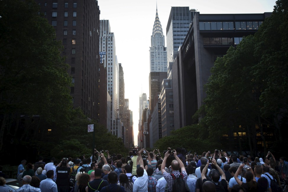 People clamor to take photos of the effect known as 'Manhattanhenge' but were thwarted by clouds from seeing the sunset in the Manhattan borough New York