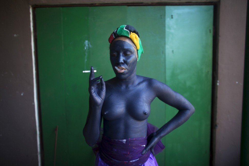 Actress Maibel Salazar, 24, smokes a cigarette before performing as part of the creation 'Mutacion Forzada', or Forced Mutation, by Cuban artist Alberto Lescay during the 12th Havana Biennial, in Havana
