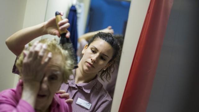 Gil Quiros of Spanish brushes resident's hair at SenVital elderly home in Kleinmachnow
