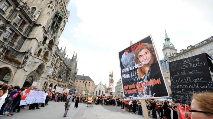 Erzieher-Ausstand: Ernste Stimmung: Mit einem Schweigemarsch ziehen Erzieher am Dienstag vor das Rathaus, um für bessere Arbeitsbedingungen zu demonstrieren.