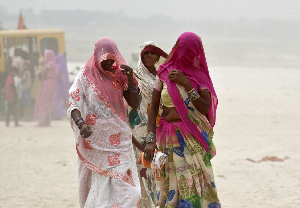 Women cover themselves as they walk on the banks of the river Ganges during a dust storm in Allahabad