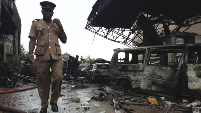 A fire services officer walks at the wreckage of a gas station that exploded overnight killing around 90 people in Accra