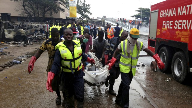 Rescue workers carry a corpse from the remains of a petrol station that exploded overnight killing around 90 people in Accra