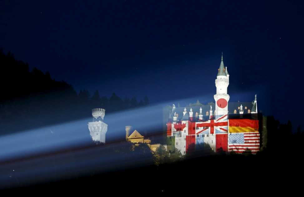 The south Bavarian castle, Neuschwanstein, is illuminated with the flags of the countries participating in the G7 summit, in Hohenschwangau