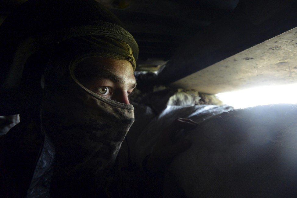 A member of the Ukrainian armed forces looks out from a blindage at his position in the village of Pisky near the local airport, outside Donetsk
