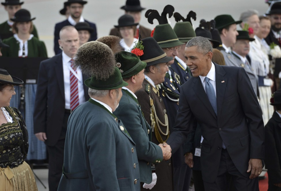 U.S. President Obama shakes hands with people in traditional Bavarian clothes during a welcoming ceremony in Munich airport