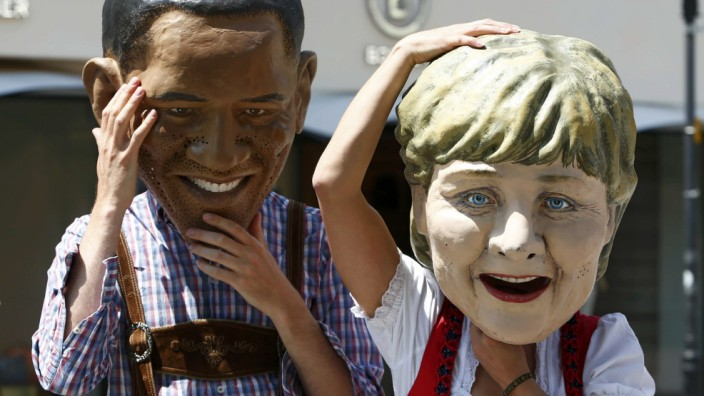 Activists of Oxfam wearing traditional Bavarian clothing and masks depicting leaders of member countries of G7 protest in Garmisch-Partenkirchen
