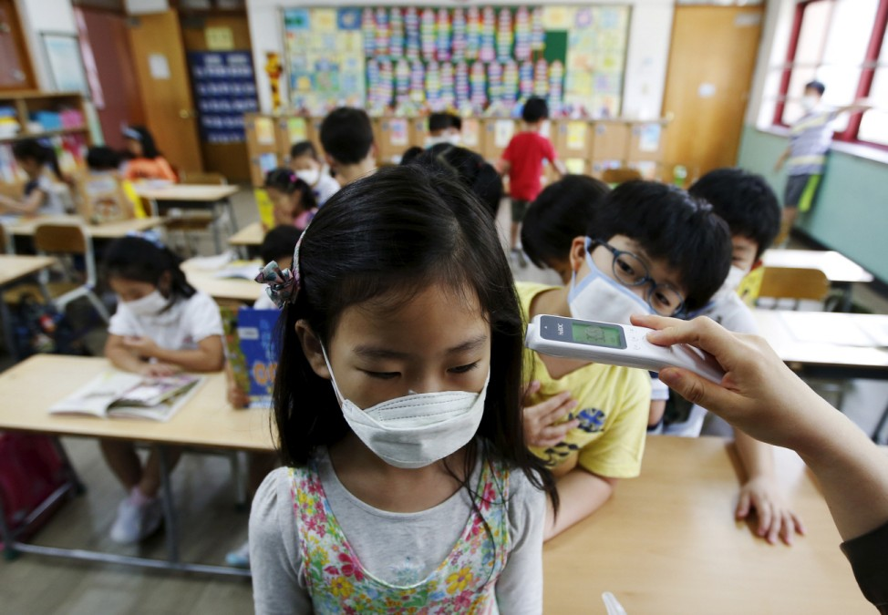 An elementary school student wearing a mask to prevent contracting Middle East Respiratory Syndrome (MERS), receives a temperature check at an elementary school in Seoul