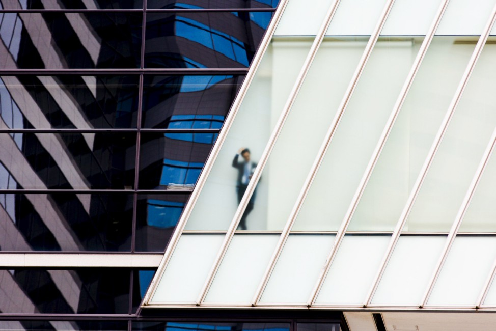 A businessman stands behind a frosted glass window of an office high-rise in central Tokyo