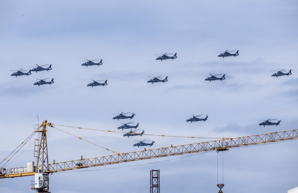 Helicopters fly in formation above a construction site in Beijing