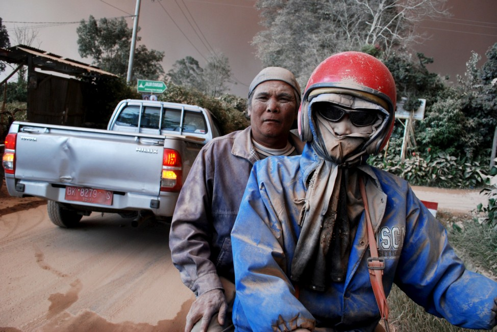 Residents with faces covered in ash ride on a motorcycle as Mount Sinabung volcano erupts, in Sukandebi village in Karo Regency, Indonesia's North Sumatra province