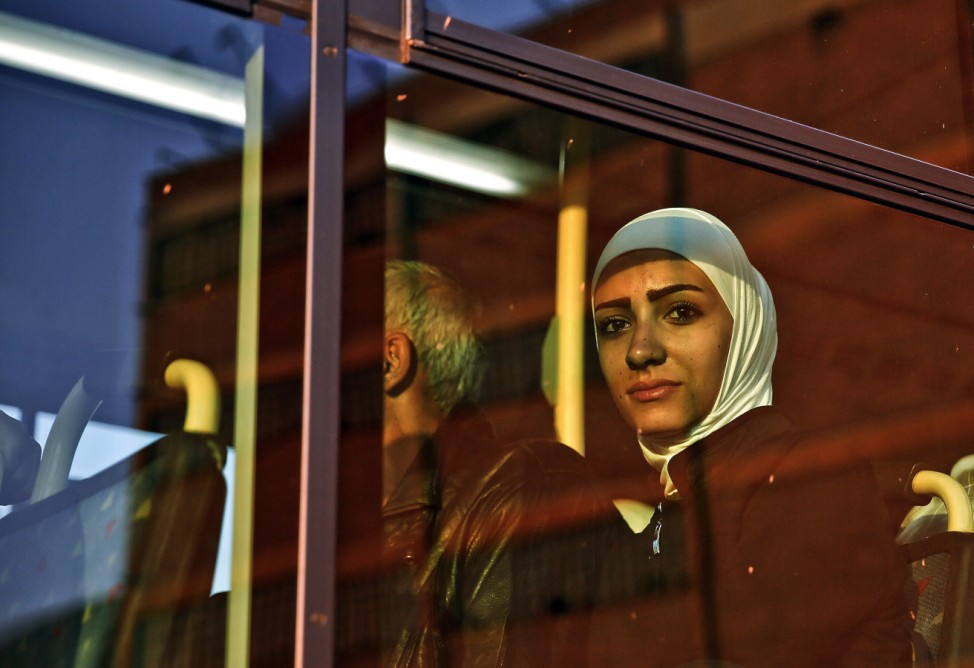 Syrian refugee woman sits in a bus after after arriving in the port of Piraeus near Athens