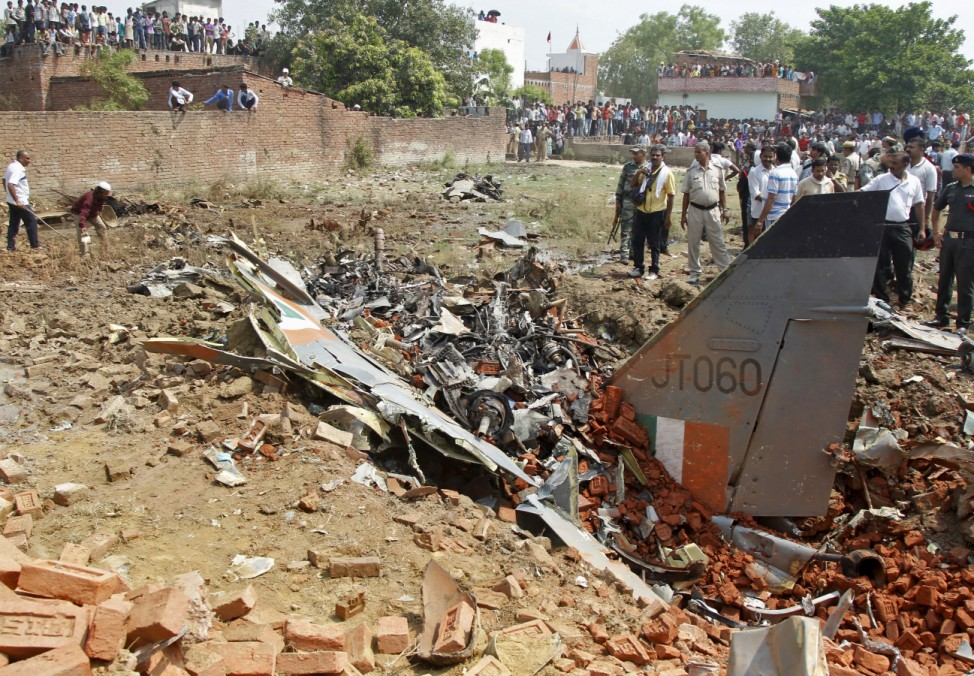Indian security personnel and onlookers stand next to the wreckage of an IAF Jaguar fighter aircraft after it crashed while on training sortie on the outskirts of Allahabad