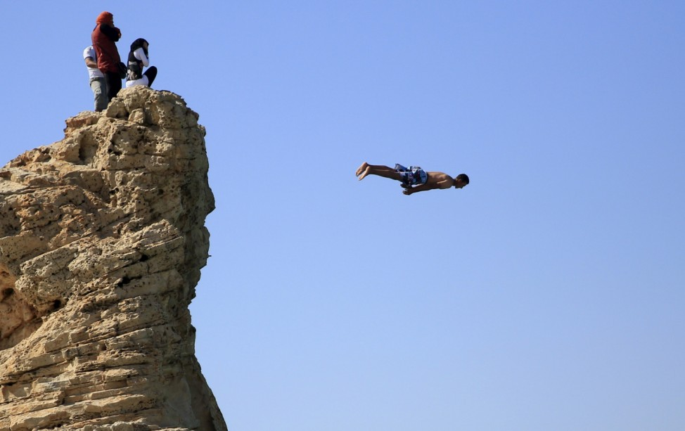 Visitors react on the rock as a man jumps into the water, above Cleopatra's Beach, on a summerâÄÖs day before the start of the holy month of Ramadan, which begins on June 18, at the Mediterranean city of Marsa Matrouh