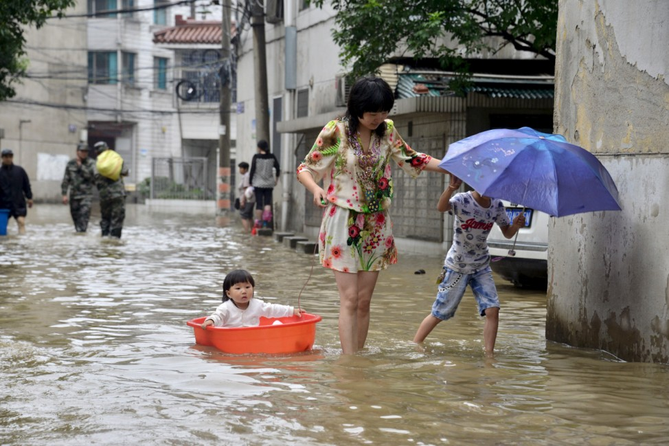 A woman with children wades through a flooded street after a heavy rainfall in Changzhou