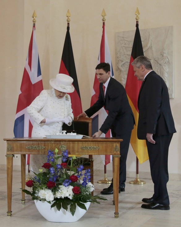 German President Gauck looks at Britain's Queen Elizabeth before signing the guest book at the Bellevue presidential palace in Berlin