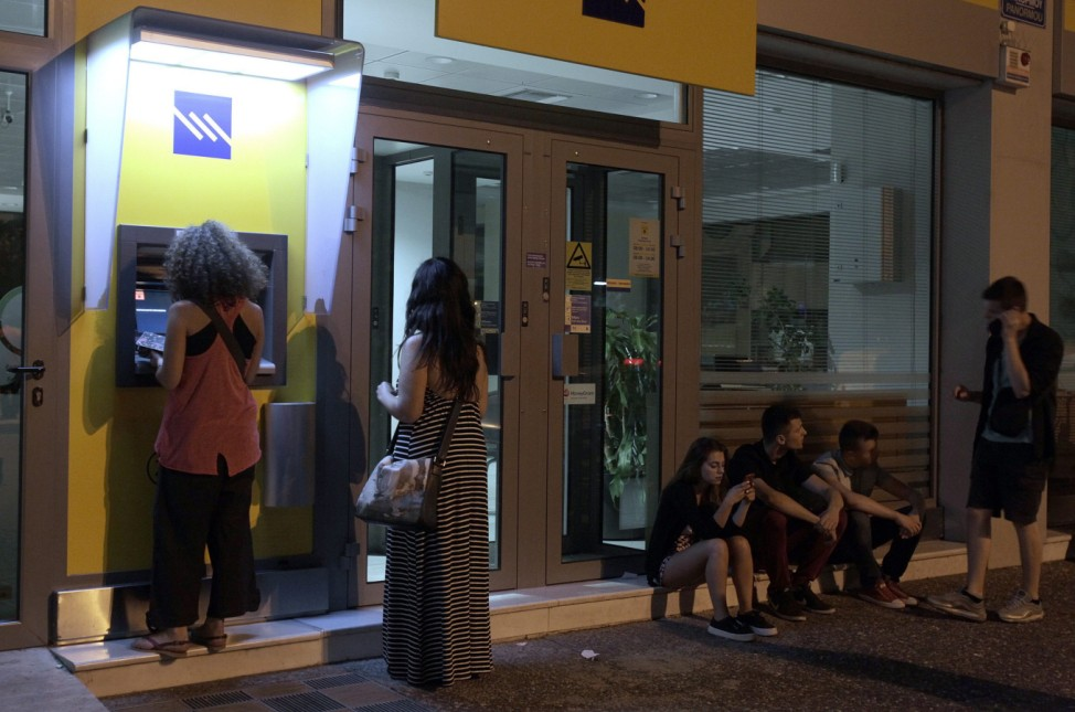 People withdraw money from ATM in Athens