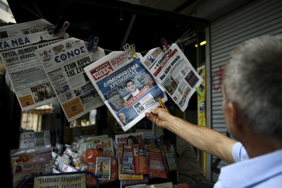 Man reads a newspaper carrying an image of Greek PM Tsipras in Athens