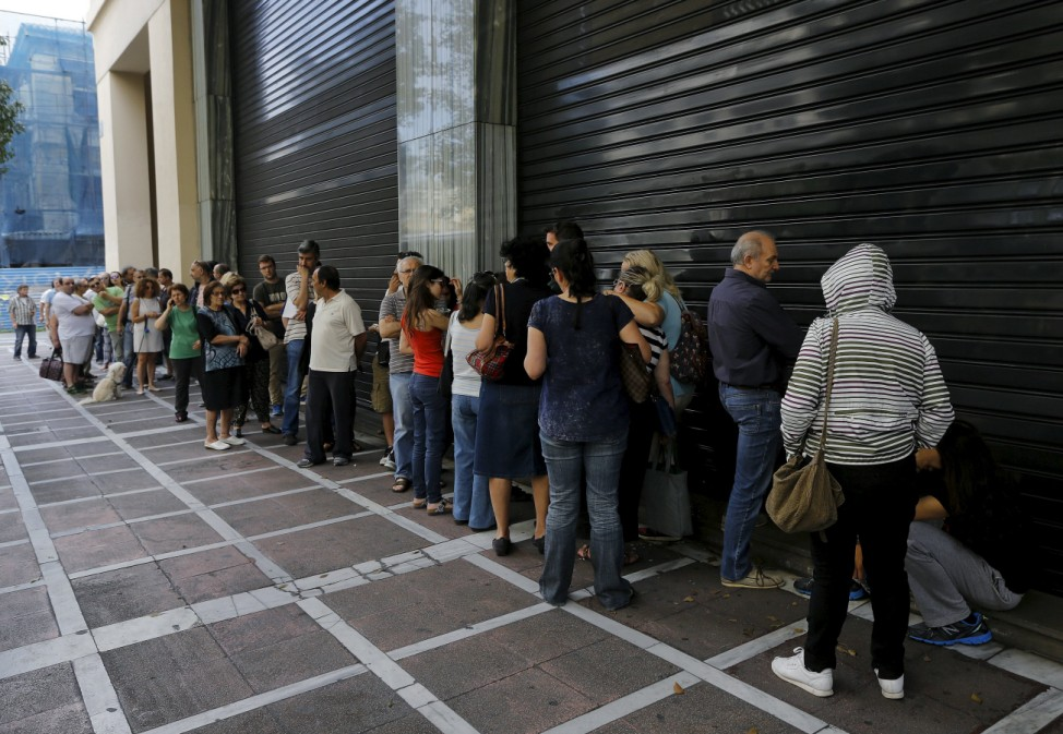 Greeks wait outside closed bank in Athens