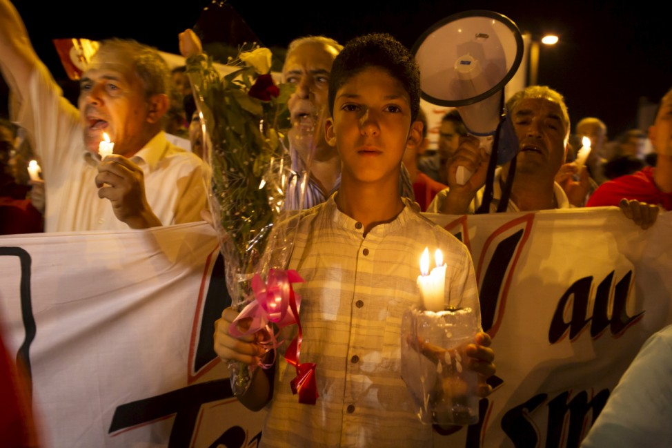 A boy holds a candle and flowers as he attends a protest to condemn the attack by a gunman at the beachside of the Imperiale Marhabada hotel in Sousse