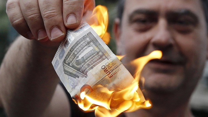 An anti-austerity protester burns a euro note during a demonstration outside the European Union (EU) offices in Athens