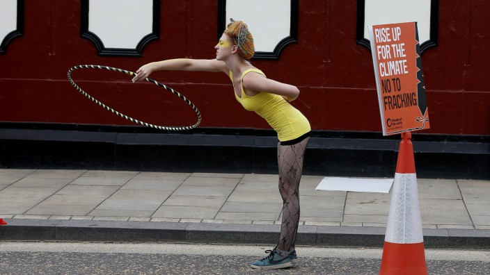 A anti-fracking protester plays with a hula hoop during a demonstration outside County Hall in Preston