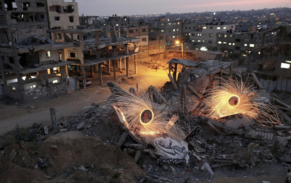 Palestinians light fireworks at Israel-Gaza conflict ruined urban