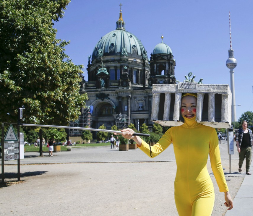 A woman from Japan films herself for an art project with a smartphone as she wears a yellow suit and a headdress in the shape of the Brandenburg Gate while walking in front of the cathedral in Berlin