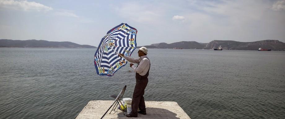 Fisherman adjusts a sun umbrella in the town of Elefsina