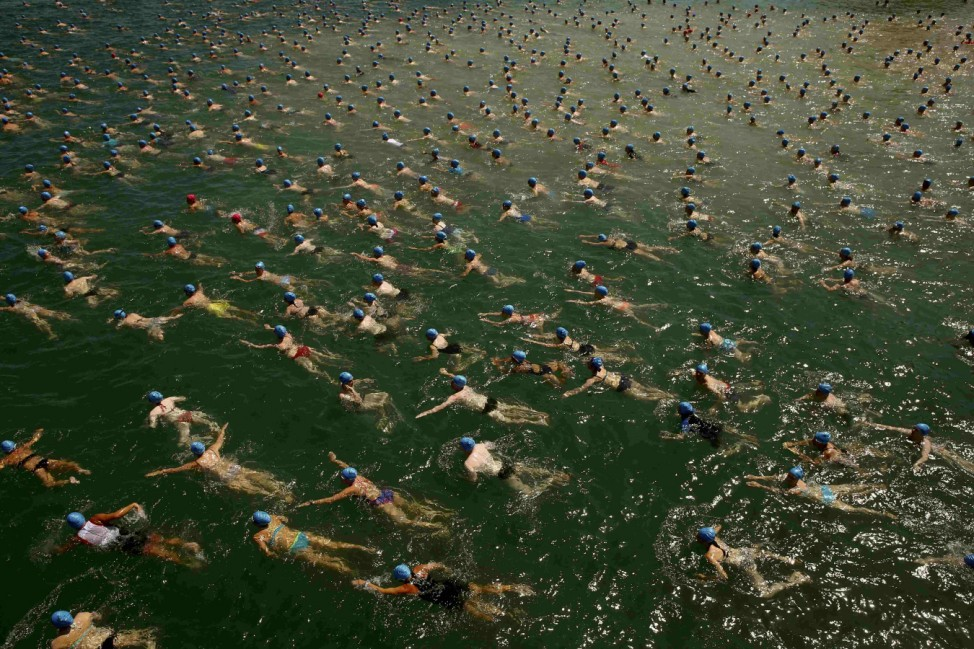 People swim during the annual public Lake Zurich crossing swimming event in Zurich
