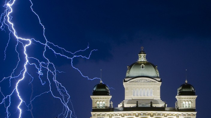 Lightning illuminates the sky during a thunderstorm over the Swiss Federal Palace in Bern