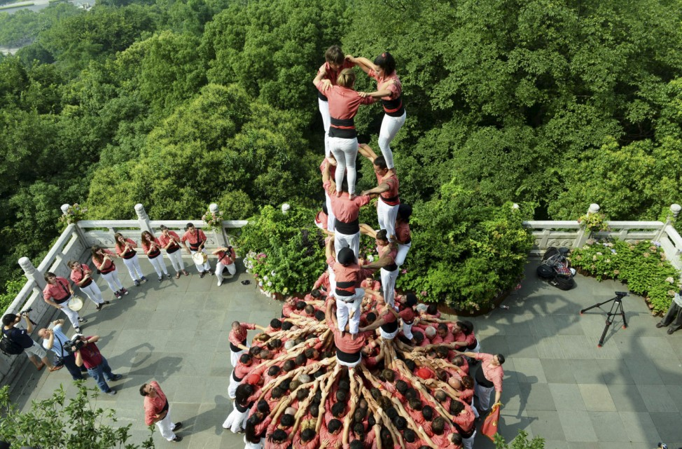 Spanish castellers form a human tower called 'castell' during a performance at the City God Pavilion a tourism resort near the West Lake, in Hangzhou