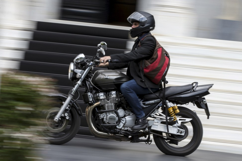 Greek Finance Minister Yanis Varoufakis leaves on his motorbike after a meeting at the office of Prime Minister's Alexis Tsipras in Maximos Mansion in Athens
