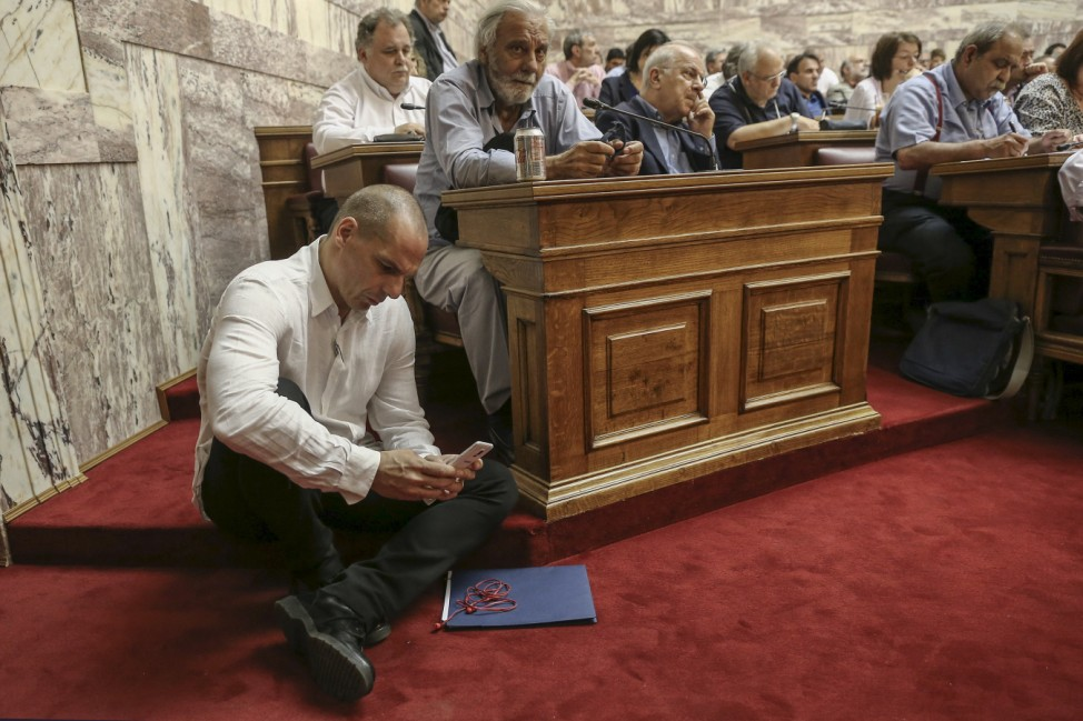 Varoufakis looks at his mobile phone while sitting on the floor during a speech of PM Tsipras to his parliamentary group at the parliament building in Athens