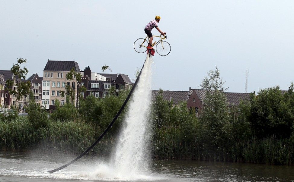 A man wearing a Tour de France best climber's jersey practises flyboarding before the start of the 166-km second stage of the 102nd Tour de France cycling race from Utrecht to Zeeland