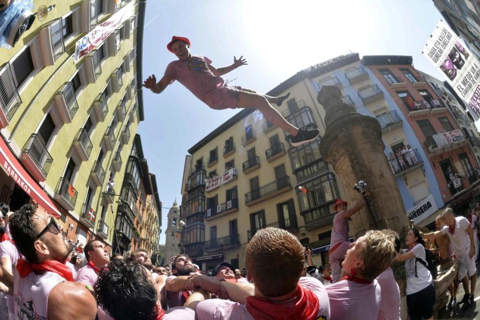 Festival von San Fermín: Ein Tourist springt von einem Brunnen in die Menge