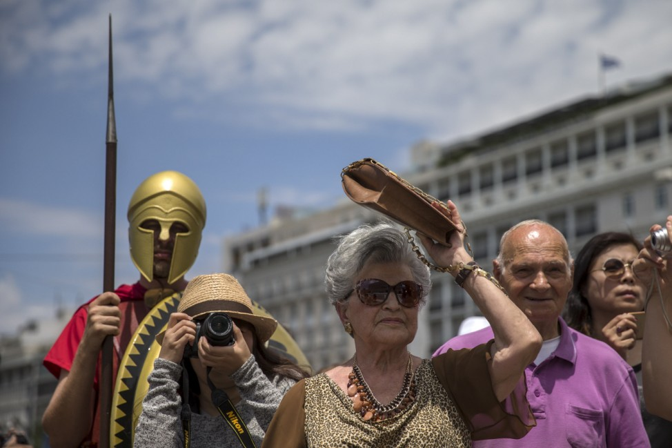 Tourists look on as they stand next to a man dressed as ancient Greek warriors during a performance at the Constitution (Syntagma) square in Athens