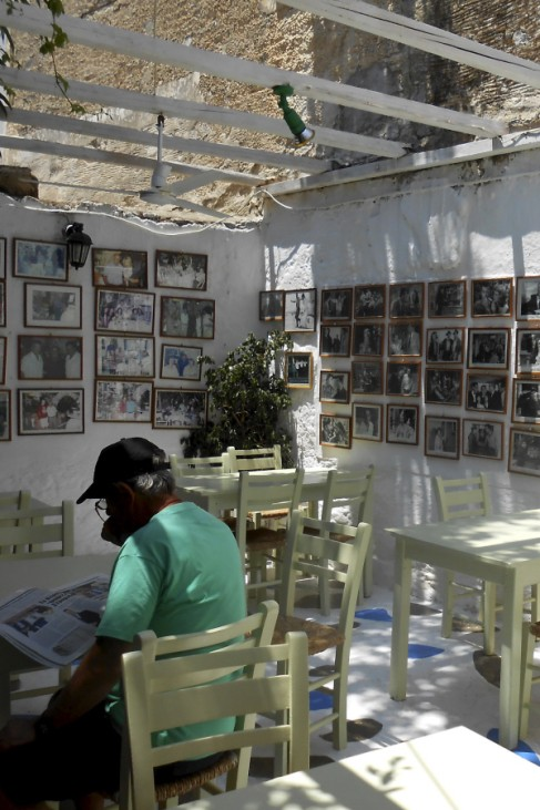 A man reads a newspaper while sitting in a taverna at the island of Paros