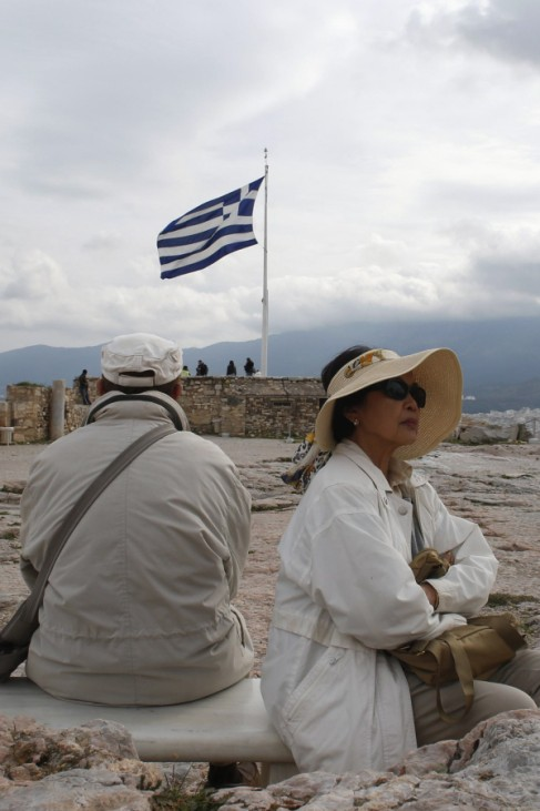 Tourists rest on a bench as they visit Acropolis hill in Athens